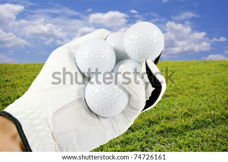 Hand holding several golf balls with a beautiful blue sky and green grass in the background