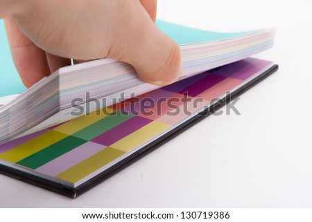 Hand holding sheets of color art book for page turn, isolated on white background.