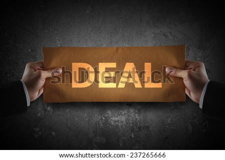 Hand holding sign deal on paper