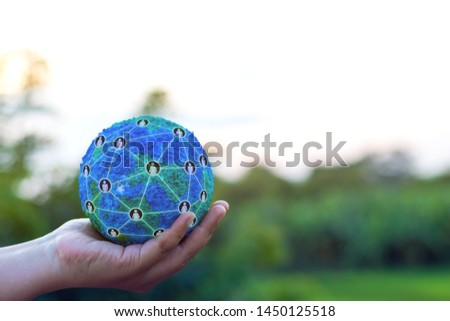 Hand holding simulated world with global structure networking social network diagram which contain people icons connected to each other stay outdoor with green tree background. Data connection concept