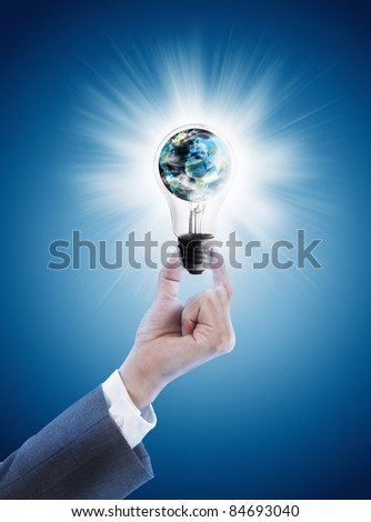 Hand holding single light bulb with globe