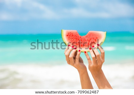 Hand holding slice of watermelon on the beach.  Colorful summer concept.  #709062487