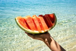 Hand holding slice of watermelon on the beach. Sea and blue sky background. Summer mood. 2021