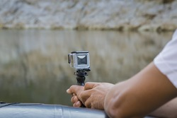 Hand holding small action camera with waterproof case and shooting from a boat on the river. Made with shallow depth of field.
