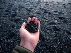 Hand holding small black rocks at Black Sand Beach, Iceland