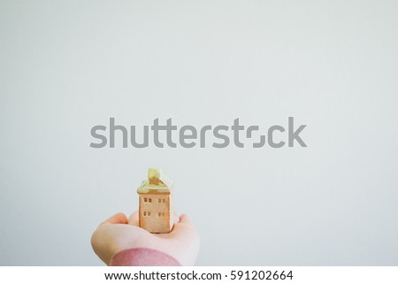 Hand holding small home #591202664