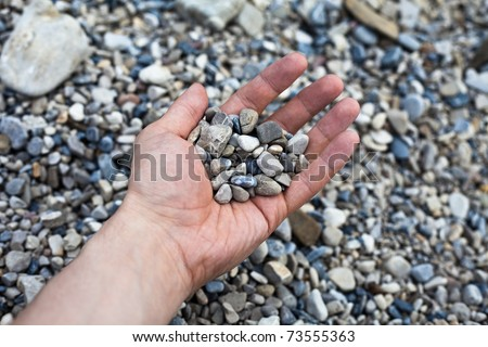 Hand holding small stones