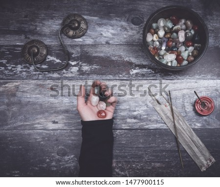 Hand holding small stones on rustic wooden table with incense sticks, a bowl of stones and Tibetan prayer bells with the words Om mani padme hum, commonly translated as The jewel is in the lotus.