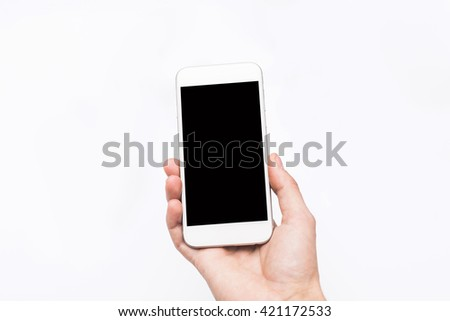 Hand holding smart mobile phone on wooden table and light blurred background #421172533