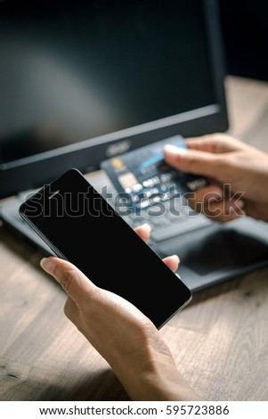 Hand holding smart phone and credit card for shopping online with laptop - Shutterstock ID 595723886