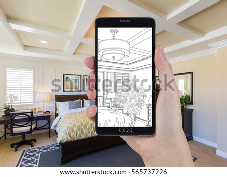 Hand Holding Smart Phone Displaying Drawing of Custom Bedroom Photo Behind.