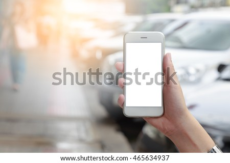 Shutterstock Hand holding smart phone isolated white screen with blurred urban people and white car parked on road
