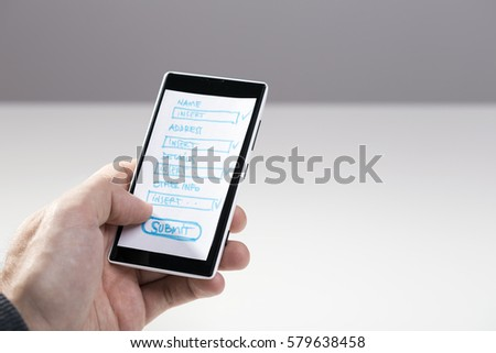 Hand holding smart phone, mock-up sketch of layout with blank form fields for mobile application #579638458