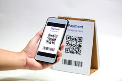 Hand holding smart phone to scan QR code payment on white background. The concept of cashless technology or digital payment.