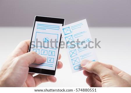 Hand holding smart phone, user interface designer checking wireframe sketch for mobile app. Prototype sketch of mobile responsive website