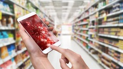 Hand holding smart phone with 3D Coronavirus or Covid-19 screen background in department store. Photo shot blurry supermarket. Smartphone technology lifestyle. Health and medical theme