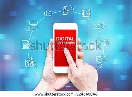 Hand holding smart phone with Digital Advertising word and icon on blue pixel blur background, Digital Marketing concpet.