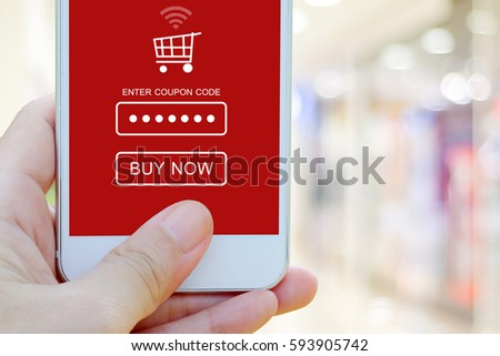 Hand holding smart phone with discount coupon code on screen over blur store background, on line shopping ,business, E-commerce, technology and digital marketing background