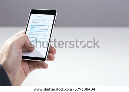 Hand holding smart phone with mock-up sketch for mobile application, responsive design, wireframe development, website log in screen #579638404