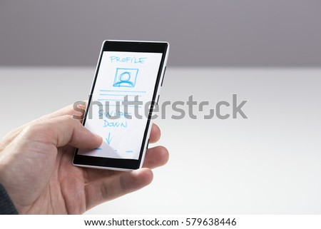 Hand holding smart phone with mock-up sketch for mobile application, responsive design, wireframe development #579638446