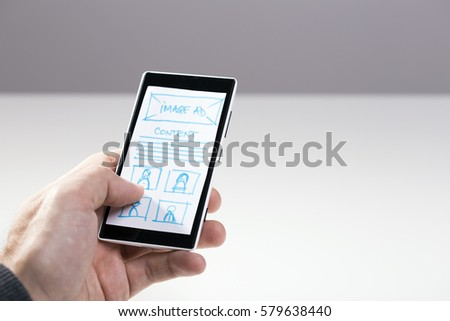 Hand holding smart phone with mock-up sketch of layout for mobile website #579638440
