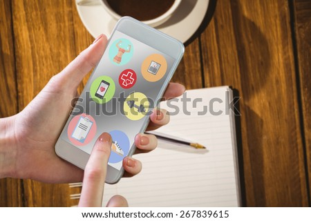 Hand holding smartphone against desk with coffee and notepad #267839615