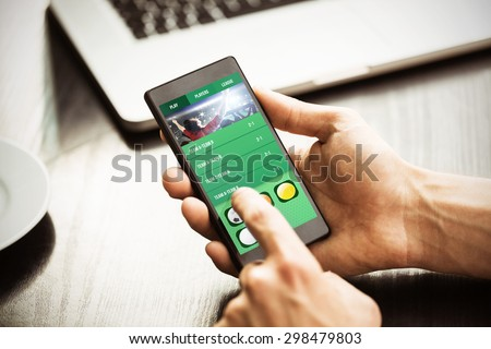 Hand holding smartphone against gambling app screen