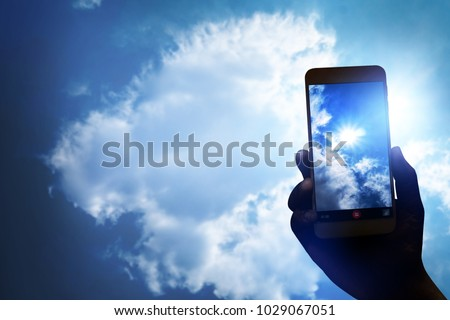 Hand holding smartphone for recording video and take photo the sun clouds sky, hi technology photography.