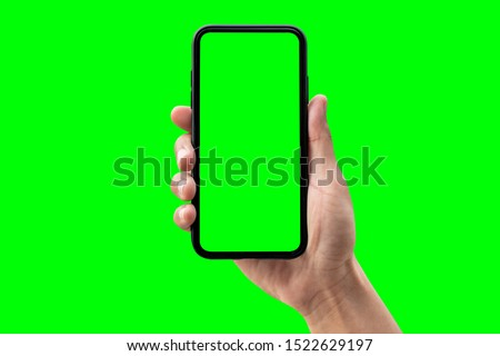 Photo of  Hand holding smartphone isolated on green background.