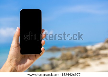 Hand holding smartphone on beach with copy space. Tourism business concept, Shopping concept, Comunication concept