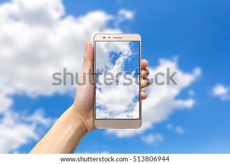 hand holding smartphone on blue sky background