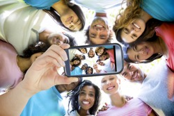 Hand holding smartphone showing friends forming huddle