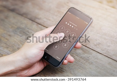 hand holding smartphone while entering the passcode. #391493764