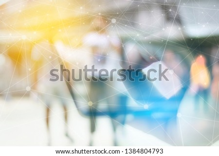 Hand holding smartphone with blurred imag of people walking in bustling shopping mall. Communication Social media Internet Of Things Concept.