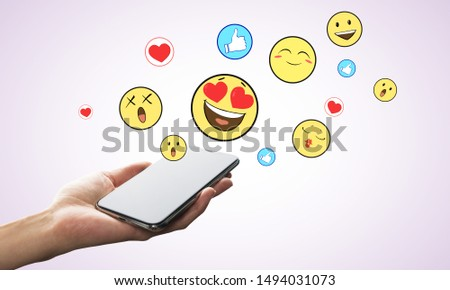 Hand holding smartphone with emotive on subtle background. Communication and emotion concept