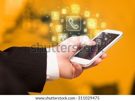 Hand holding smartphone with glowing mobile app icons #311029475