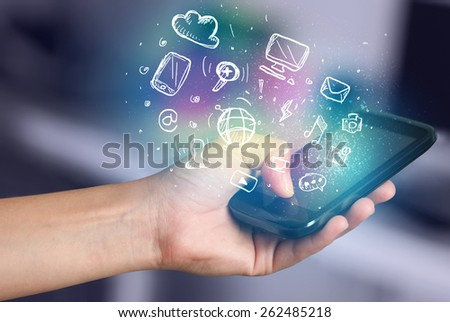 Hand holding smartphone with glowing multimedia icons  #262485218
