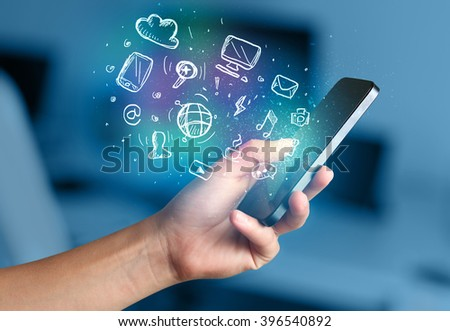 Hand holding smartphone with glowing multimedia icons  #396540892