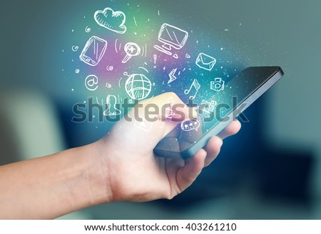 Hand holding smartphone with glowing multimedia icons  #403261210