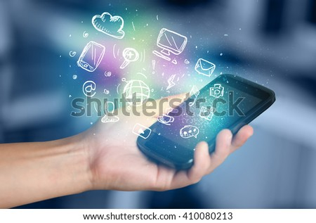 Hand holding smartphone with glowing multimedia icons  #410080213