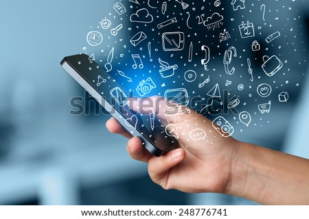 Hand holding smartphone with hand drawn media icons and symbols concept #248776741