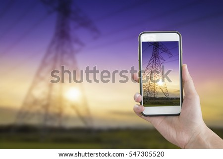 Hand holding smartphone with high voltage pole background. #547305520