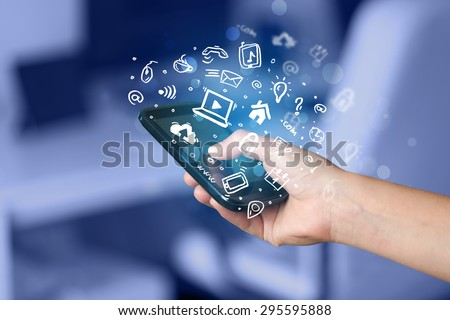 Hand holding smartphone with media icons and symbol collection #295595888