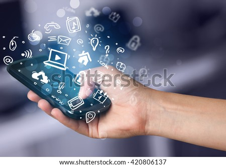 Hand holding smartphone with media icons and symbol collection #420806137