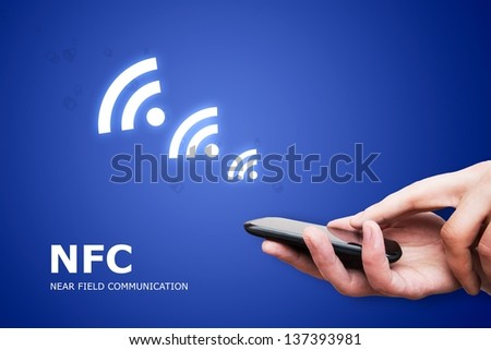 Hand holding smartphone with NFC technology - near field communication payment method