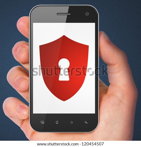 Hand holding smartphone with shield with keyhole on display. Generic mobile smart phone in hand on dark blue background.