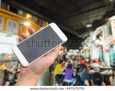 Hand holding smartphone with street foods hawker hall background #447670705