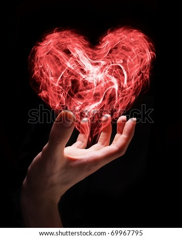 Hand holding smoke heart as a symbol of fragile nature of love or can symbolize someone giving love.