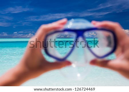 Hand holding snorkel goggles against tropical beach and sky