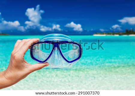 Hand holding snorkel googles against blurred beach and blue sky #291007370